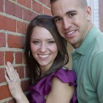 Engaged couple by brick wall